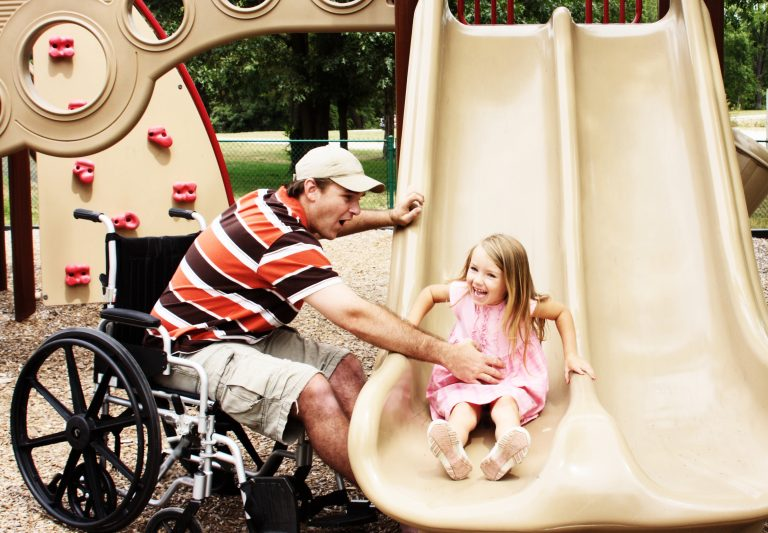 A man in a wheelchair catching a young girl on a swing