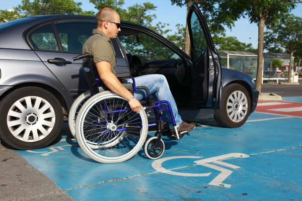Man in wheelchair next to a car near a mobility parking sign