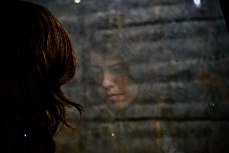 A young woman looking sadly out a window, with her face reflected.