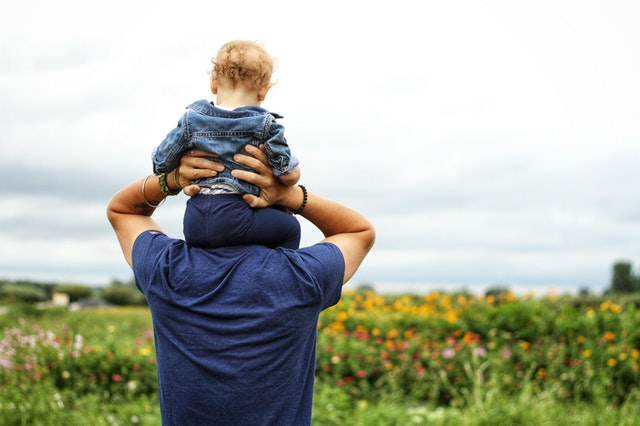 A photo of a baby on top of a man's shoulders
