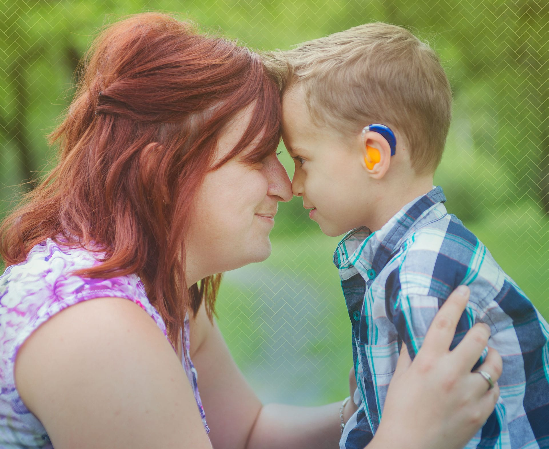 Woman performing hongi with young boy wearing a hearing aid