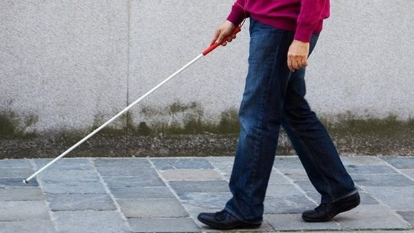A man walking on a footpath holding a cane out in front of him.