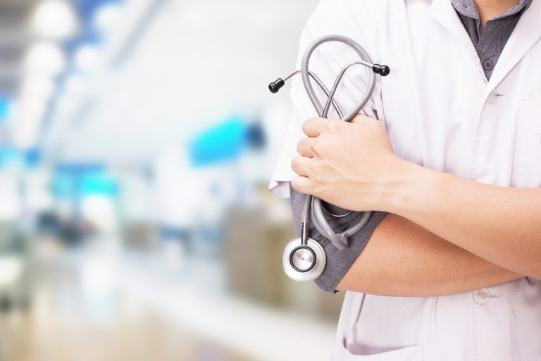 Doctor with a stethoscope in the hands and hospital background.