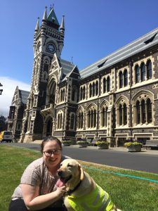 A young woman and a service dog in front of University of Otago buildings.